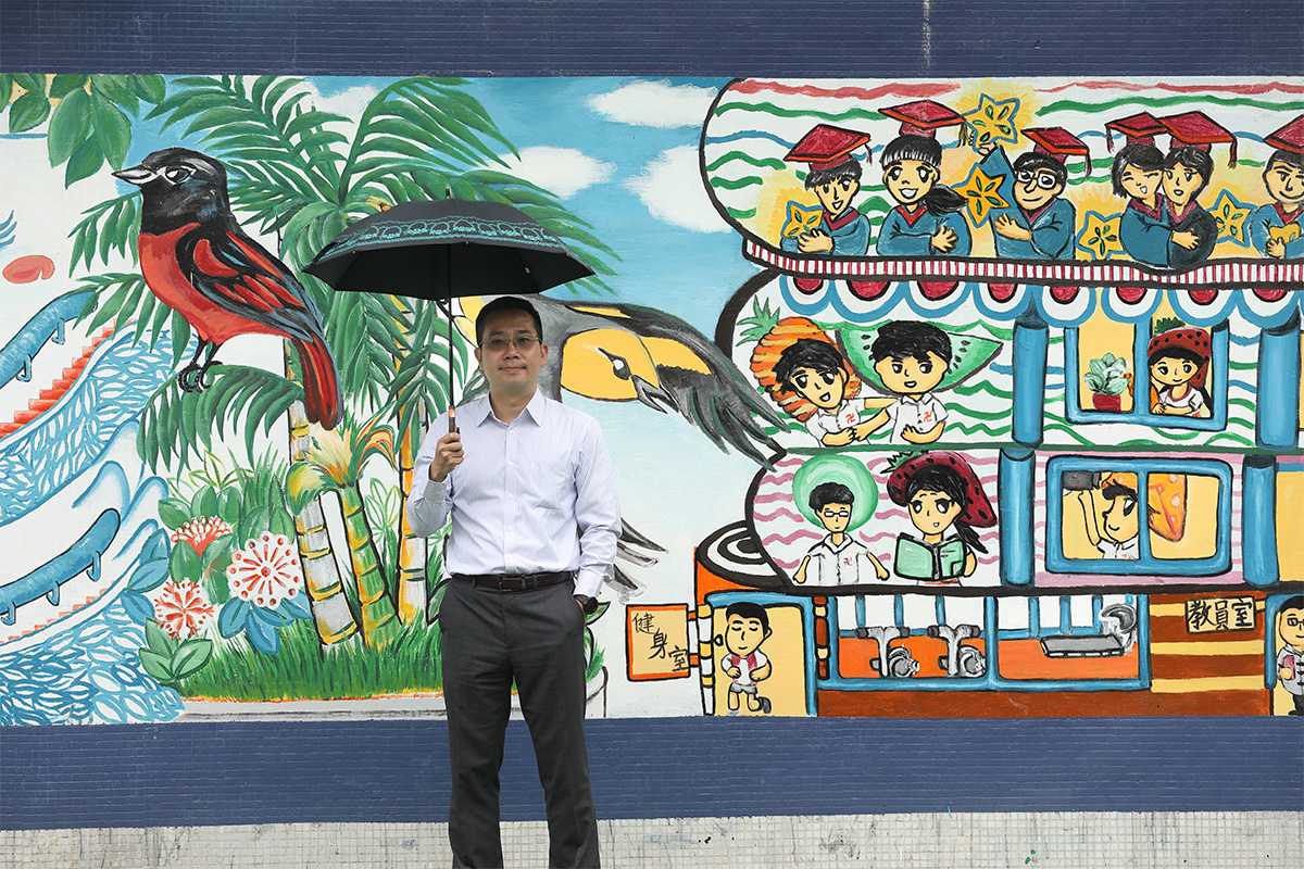 The massive wall painting behind Franky Poon is painted by a group of students led by a last year's graduate. She is now studying fine arts in Taiwan.