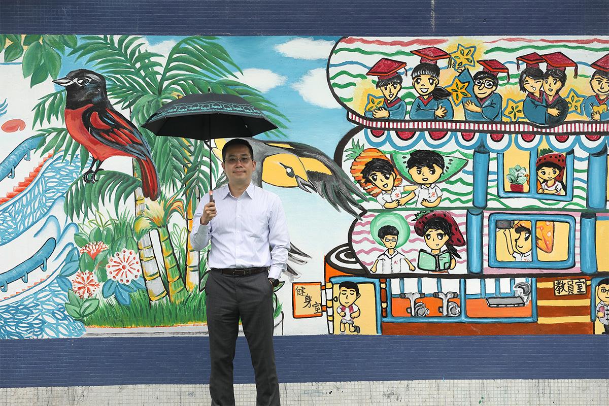 潘啟祥背後,學校操場的大型壁畫,由去年的畢業生帶領同學所畫。她現於台灣修讀美術系。